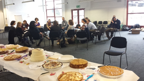 A table full of cake and people sitting and talking.