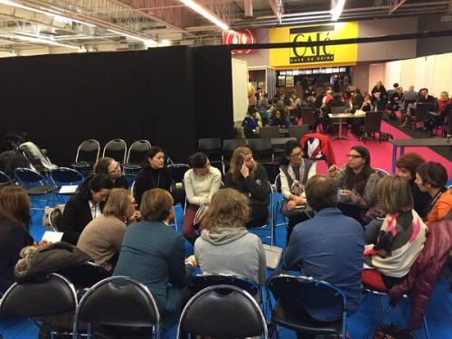 People talking to each other, sitting on chairs arranged in a circle.
